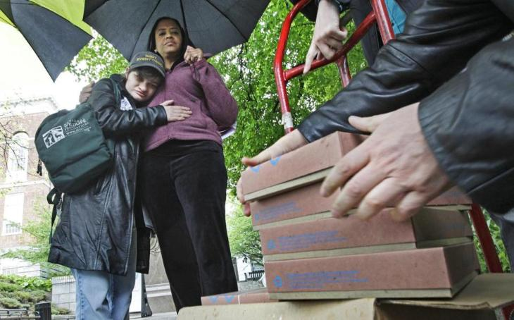Emily Titon, a short white person, hugging Cheryl McCollins, a tall Black woman, in the rain, while unloading boxes with printed signatures on a petition to ban the shocks.