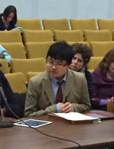 Lydia sitting at witness table to testify before Massachusetts legislature.