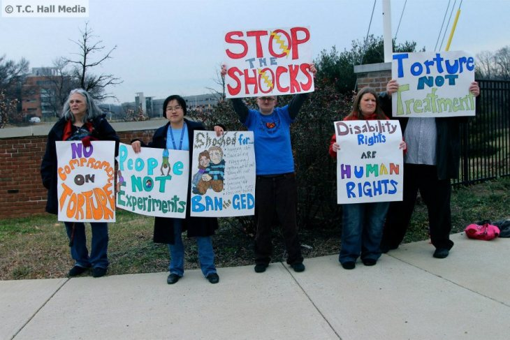 "Photo: Five people (four white, one east asian) holding hand-made protest signs outside the Food and Drug Administration's White Oak Campus in Maryland. The signs say, ""No Compromise on Torture,"" ""People Not Experiments,"" ""Shocked for... hugging staff, swearing, nagging, getting out of seat, taking off coat, screaming, tensing up, closing eyes, raising hand. BAN the GED.,"" ""Stop the Shocks,"" ""Disability Rights are Human Rights,"" and ""Torture Not Treatment."" Left to right: Diane Engster, Lydia X. Z. Brown, Shain M. Neumeier, Kathleen Nicole O'Neal, and Patrick T. Ayers. Photo by Taylor C. Hall. January 2013.."